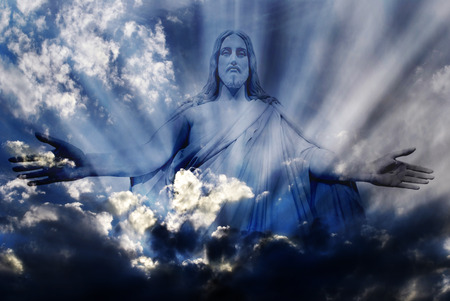 30575602 - jesus standing in white and gray storm clouds in blue sky with rays of light